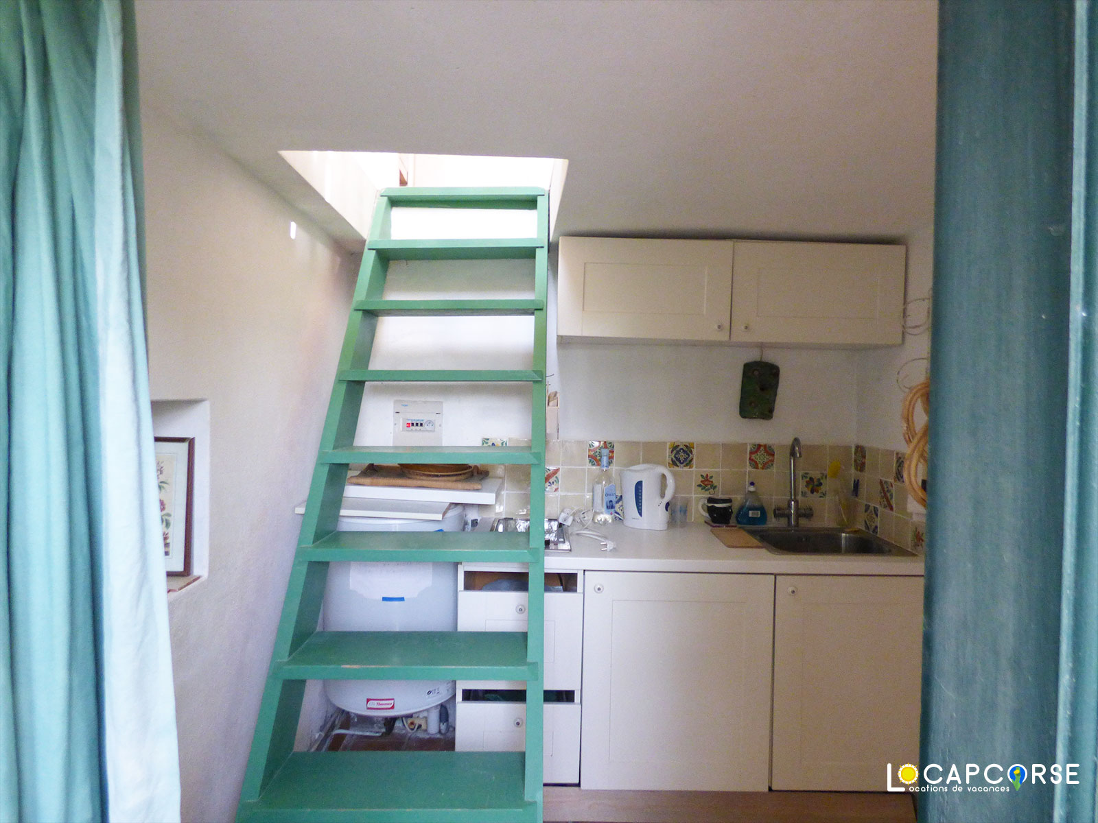 Locations Cap Corse - The kitchenette of the cottage and the internal staircase accessing the bedroom